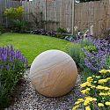 Rainbow sandstone sphere in a town house garden.