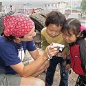 Children looking at themselves on a digital camera, China.