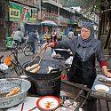Woman cooking in street, Muslim Quarter, Lanzhou, China.