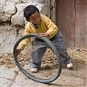 Child playing with tyre, Gyantse, Tibet.